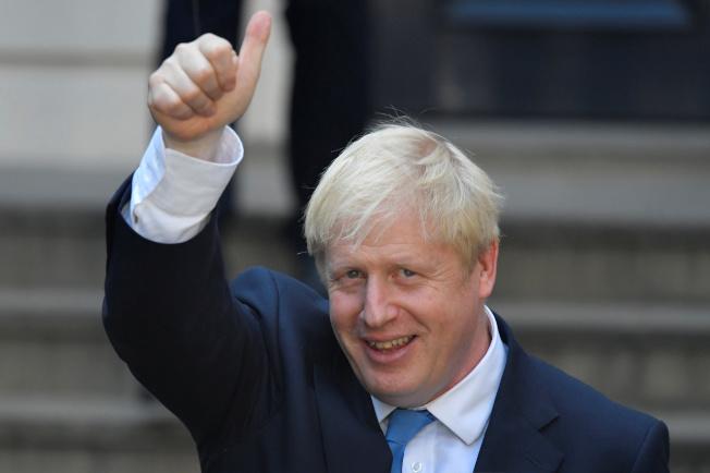 強生當選英國保守黨黨魁,即將出任首相,圖為強生23日離開保守黨總部時,向媒體伸出大拇指。(路透)