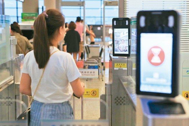 7月15日起,上海虹橋機場2號航站樓全面上線「無紙化」安檢,無托運行李旅客在值機、安檢和登機的過程中不再需取任何紙質登機牌和安檢憑條。圖為旅客在安檢口刷臉,查核身分。 中新社
