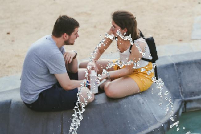 比利時24日出現攝氏38.9度高溫,刷新該國紀錄,圖為兩名在布魯塞爾市區一處噴泉旁休息的遊客。(新華社)