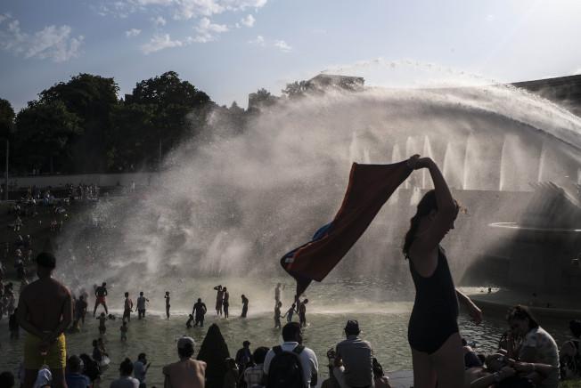 巴黎居民和遊客跳進噴泉,盡情享受夏日清涼。(美聯社)