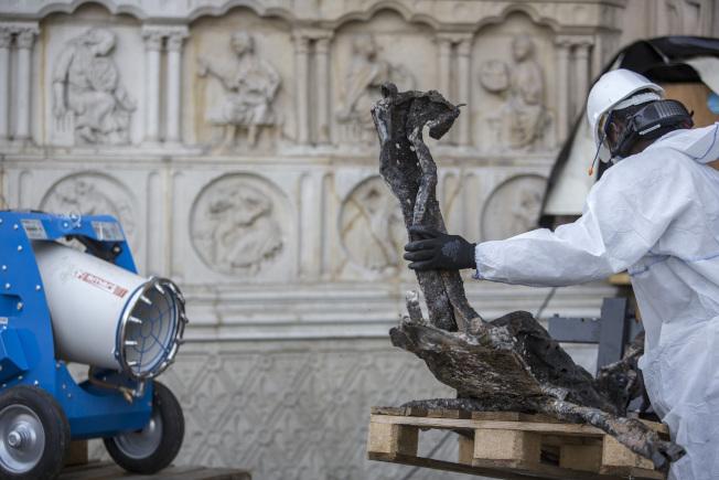 整修人員穿著包裹全身的防護衣,在高溫下搶修遭大火洗禮的聖母院古蹟。(美聯社)