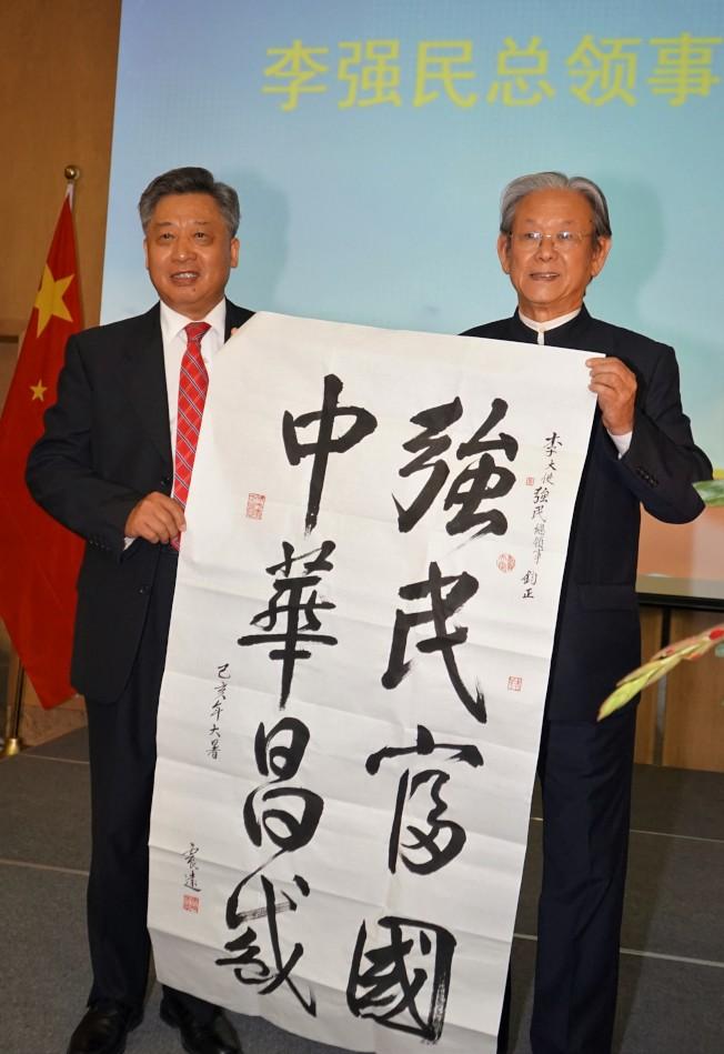 書法家江鎮遠(右)向李強民贈送書法作品。(記者賈忠/攝影)
