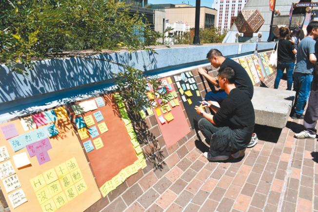 參加者在連儂牆上貼小貼紙,控訴港府「暴政」。(本報記者/攝影)