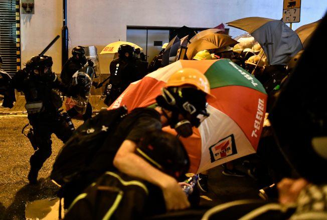 示威者撐起雨傘,站在一塊,希望抵擋警力。(Getty Images)