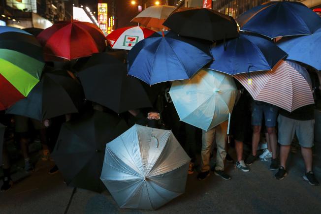 示威者撐起雨傘,站在一塊,希望抵擋警力。美聯社