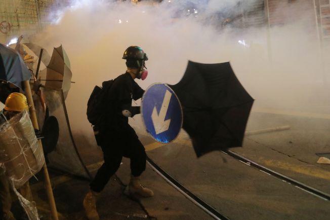 香港反送中抗議群眾28日在中環集會,以雨傘對抗警方的催淚彈。(Getty Images)