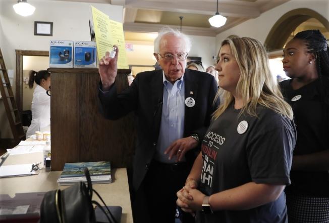 民主黨總統參選人桑德斯(左)28日陪同一個糖尿病購藥團,赴加拿大溫莎市一家藥店購買胰島素。(美聯社)