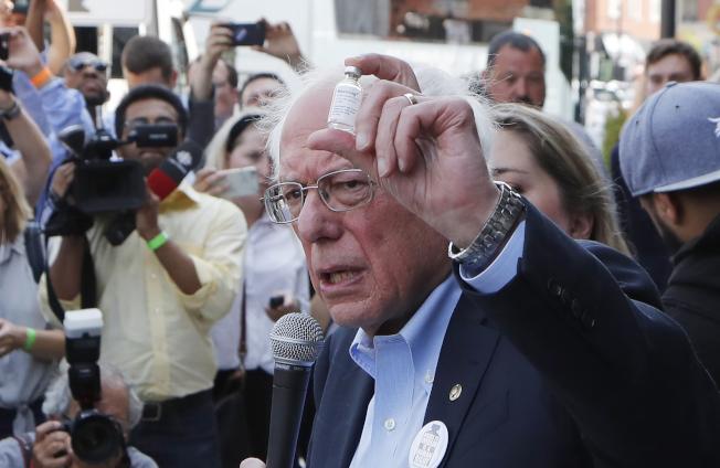 民主黨總統參選人桑德斯28日在加拿大溫莎市一家藥店前,手持一小瓶胰島素,痛批美國的高藥價。(美聯社)