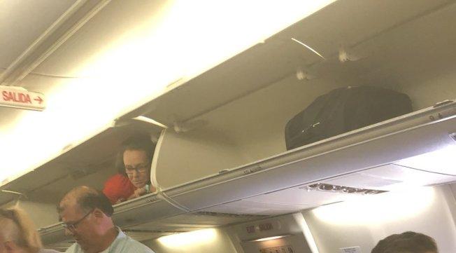 西南航空的一名空服員在登機時躲在行李架上和乘客打招呼。取材自推特