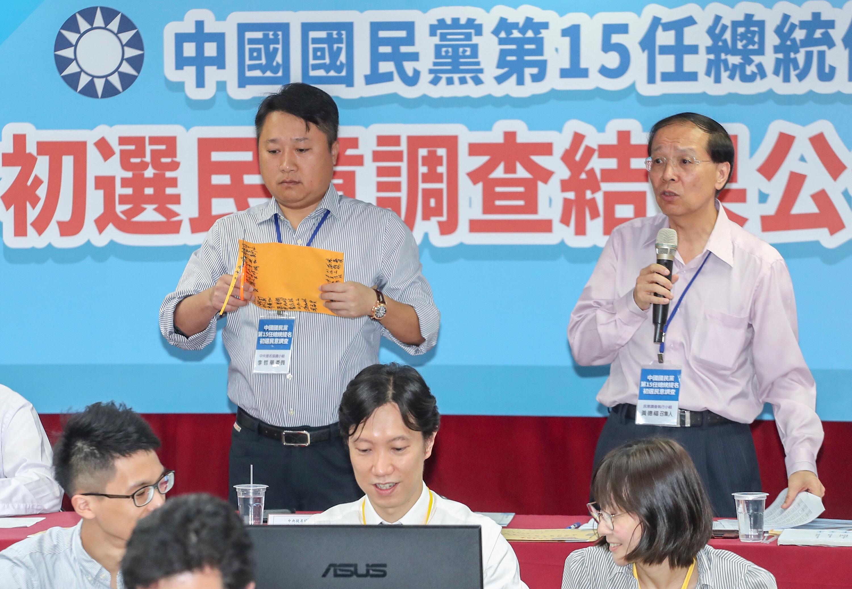 中國國民黨總統初選民意調查15日在中央黨部揭曉,民意調查執行小組召集人黃德福(後右)與中央提名協調小組委員李哲華(後左)將民調信封開封。(中央社)