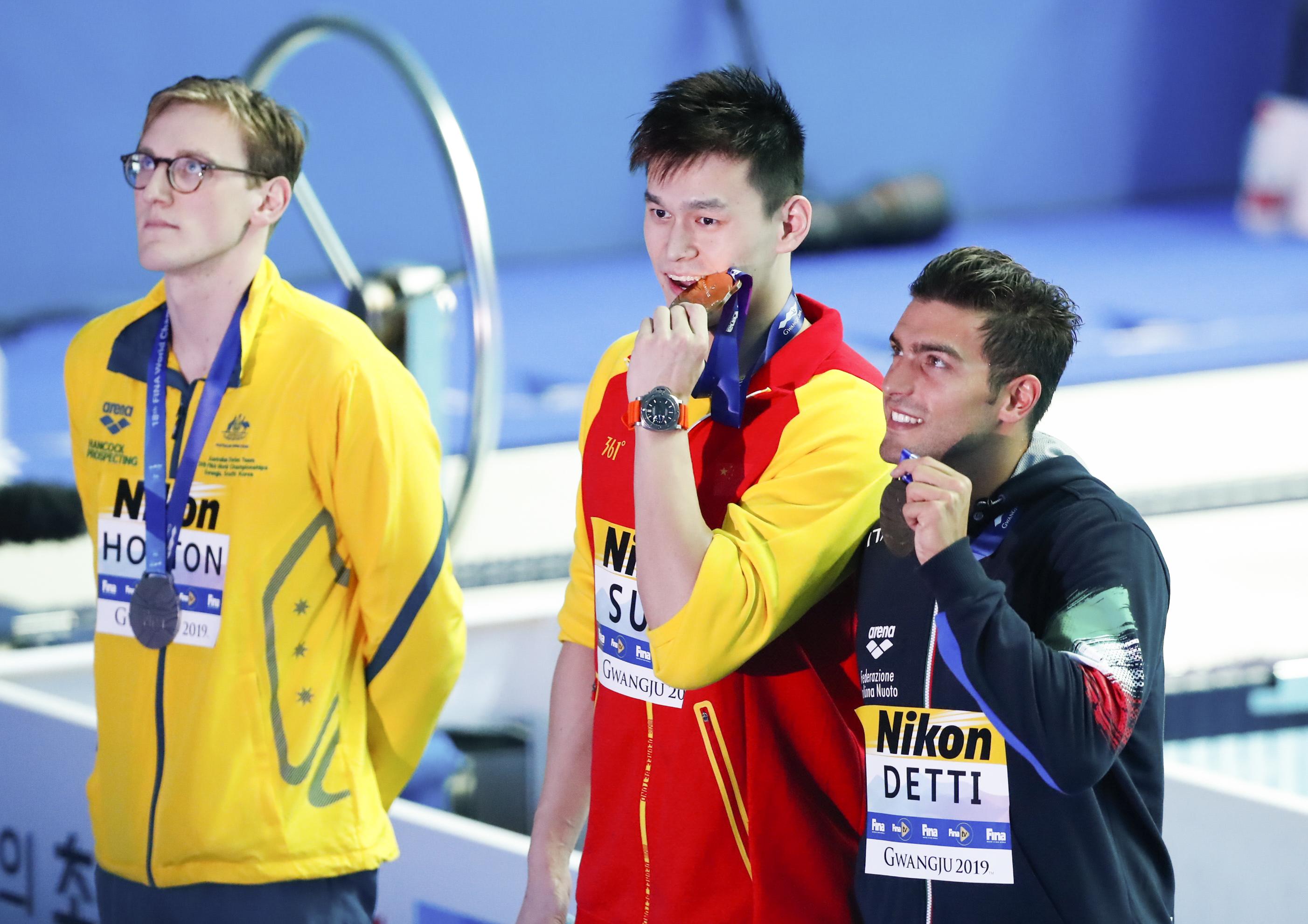 中國選手孫楊(中)、澳洲選手霍頓(左)和義大利選手德蒂分獲冠、亞、季軍後在泳池邊接受記者拍照。新華社