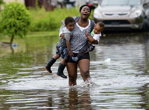 一名母親帶著孩子涉水。(美聯社)