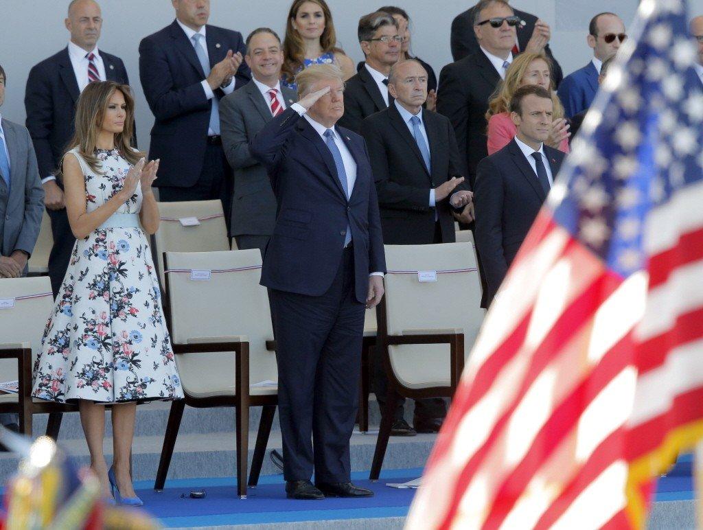 川普(前中)和第一夫人梅蘭妮亞(前左)去年七月在法國總統馬克宏(前右)陪同下,參加法國國慶閱兵。(美聯社)