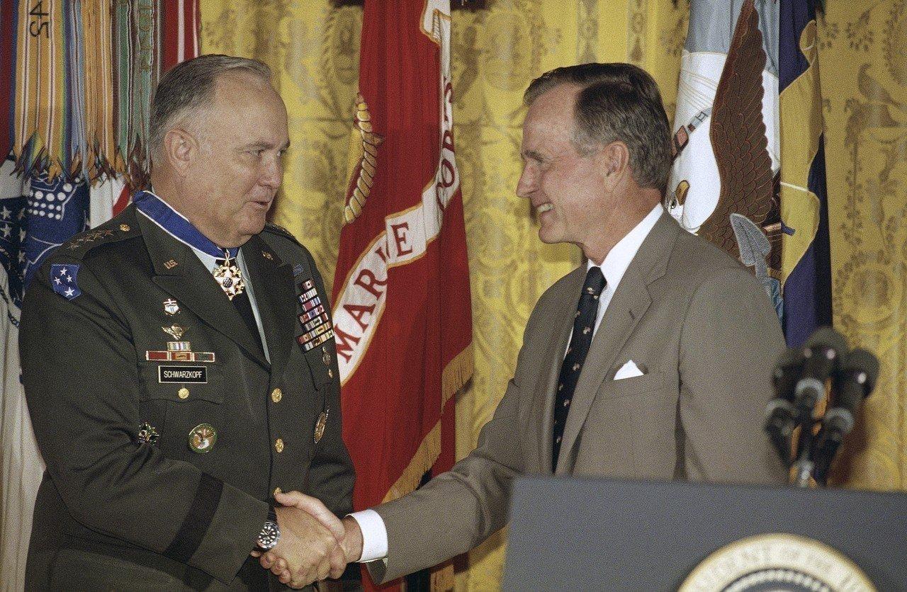 老布希(右)1991年國慶頒獎給「沙漠風暴」指揮官史瓦茲柯夫將軍。(美聯社)