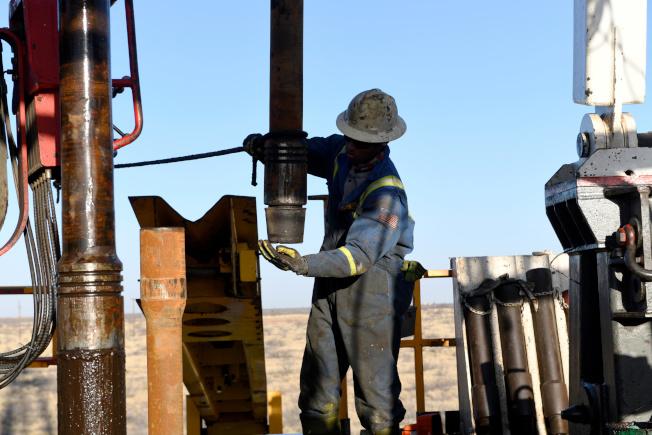 美中貿易戰升高,可能影響原油消耗,使油價下跌。圖為德州一個油井正在鑽油。(路透)
