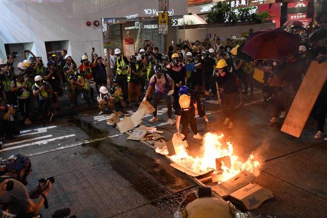 旺角区聚集的示威者3日晚将大量液体倒在木梯上,随后点燃,试图阻挡警察推进。(中通社)