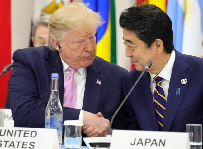 圖為川普與安倍兩人在6月底大阪峰會上握手畫面。路透
