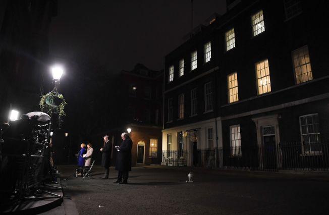 1月15日英國議會對脫歐協議進行投票表決,當晚媒體記者守在官邸外直播,賴瑞貓站在不遠處。(Getty Images)