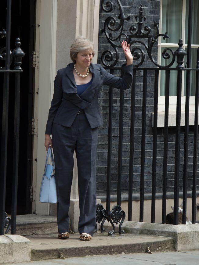 2016年,梅伊在官邸門口與民眾揮手,此時她即將接替卡麥隆成為首相。在一旁休息的賴瑞回頭望向她。(Getty Images)