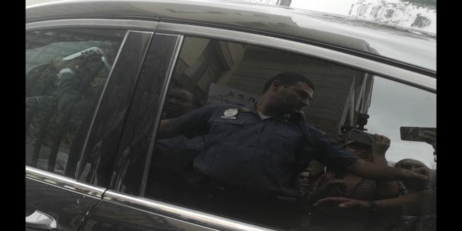 卡蘭扎乘坐黑色車窗的車輛進入學校,抗議者對著車窗大喊。「記者黃伊奕/攝影」