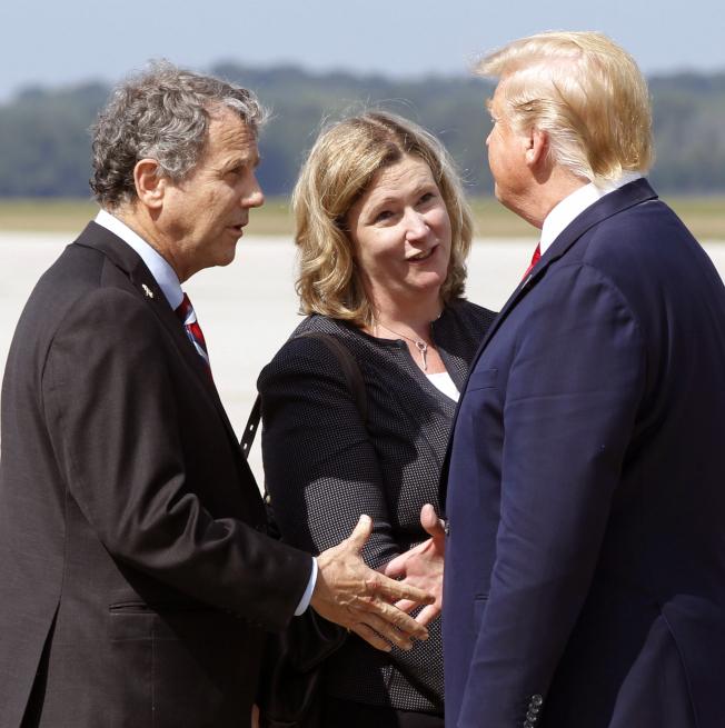 川普總統(右)赴俄亥俄州岱頓市慰問槍擊案被害人及救援人員,在機場受到岱頓市長惠利(中)和民主黨籍參議員布朗(左)的歡迎。(美聯社)