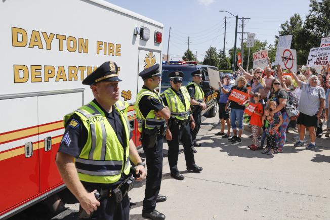 川普總統到俄亥俄州岱頓慰問救援人員及槍擊案傷者,大批民眾到場抗議,警察及消防人員排出人牆把抗議人群隔開。(美聯社)