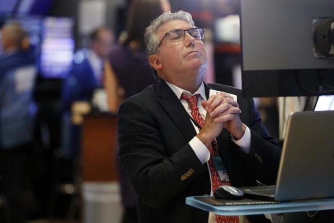 擔心美中貿易大戰,華爾街受到衝擊,道瓊指數一度下跌近600點,圖為紐約證券交易所交易員雙手合十,看著大盤走勢。(美聯社)