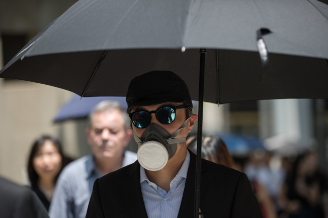 香港法律界7日再度舉行靜默遊行,與上次一樣身著黑衣,但有遊行者舉著雨傘、戴上頭盔和口罩,以示抗議。(歐新社)