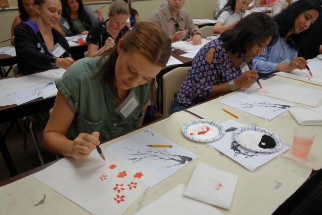 爾灣學區教師們在研習會中嘗試拿毛筆畫國畫。(照片由南海岸中華文化中心提供)