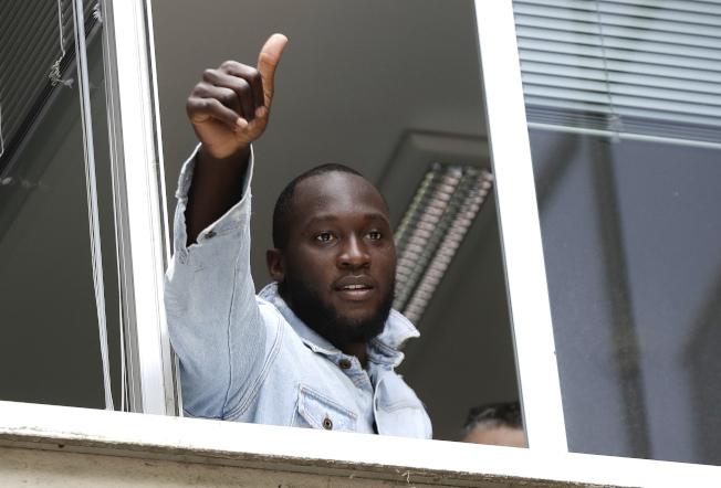 盧卡庫8日在國米基地簽約後,向窗外的球迷致意。(美聯社)