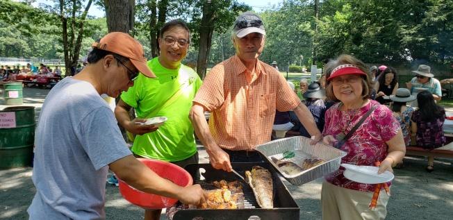 陳富雄(右二)帶來一大冰桶自釣鮮魚,還親自上陣做燒烤服務。(記者唐嘉麗/攝影)