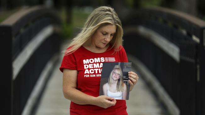 2007年猶他州鹽湖城Trolley Square購物中心槍擊案的受害者卡洛琳.塔夫特,至今體內仍有300顆散彈槍的鉛彈。 她所持的照片是在槍案中喪生的15歲女兒克絲汀。(美聯社)
