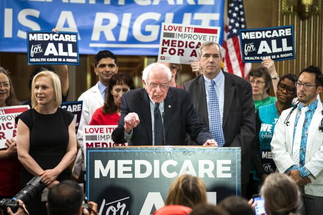 面對高昂藥價,國會參院提案要保護納稅人。圖為參院民主黨議員桑德斯(中)、陸天娜(前左)等人日前呼籲推行全民健保。(歐新社)