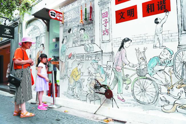 上海泰康路田子坊1號門的一幅石庫門畫吸引遊客注意。畫中煙紙店、公用電話亭、皮匠修鞋攤、剃頭師傅等老上海的生活場景,勾起老上海人回憶。(中新社資料照片)