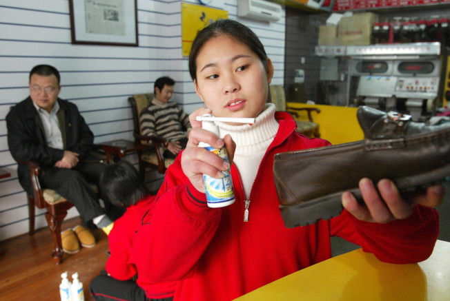 上海市中心城區內的一家鞋吧員工在為護理後的皮鞋噴灑香水。(新華社資料照片)