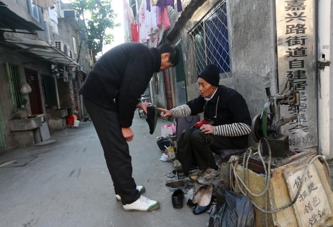 上海虹鎮老街修鞋師傅(右)在老街的街角招攬生意。(新華社資料照片)