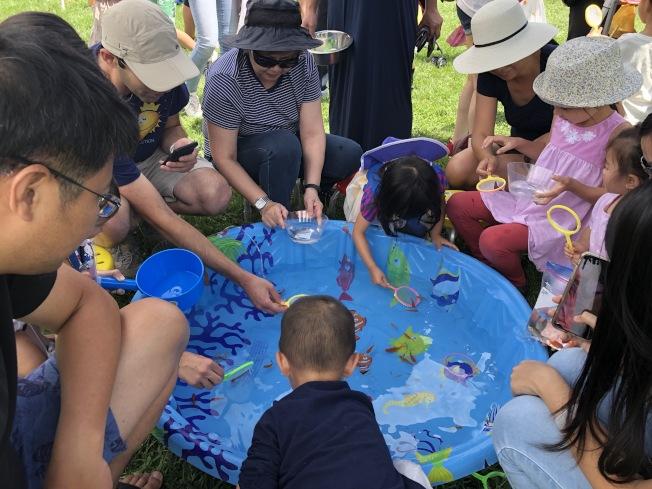 遊戲區中最受歡迎的是撈魚攤,且聚集許多家長帶著小朋友協力完成任務。(記者林亞歆/攝影)