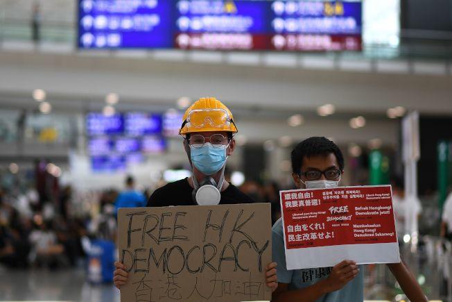 香港國際機場11日繼續有反送中示威者擔牌,以標語向國際旅客宣達反送中的目的。(美聯社)