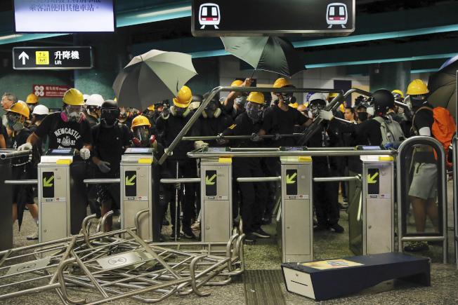 反送中示威者11日在地鐵鰂魚涌站架設鐵欄,準備迎戰港警的鎮壓。(美聯社
