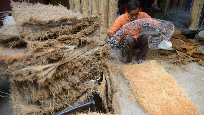 一名印度工人正在編織草蓆,為製作「稻草冷氣」作準備。圖擷自The National