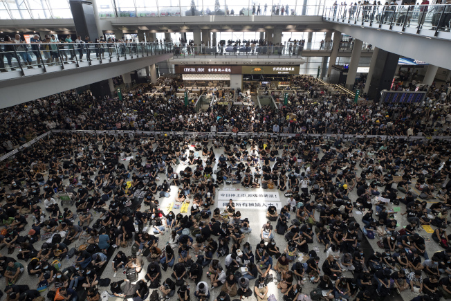 黑衣抗议群众今天涌入香港机场,声援眼睛遭警方打伤女子,入境大厅很快变成一片黑海。美联社