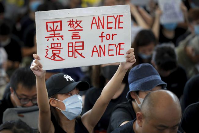 據傳港警在11日衝突中,用塑膠子彈射傷一名女性反送中示威者的眼睛,恐有失明之慮。在12日香港機場靜坐的反送中示威都就舉起「以眼還眼」的招牌抗議警方暴力。(美聯社)