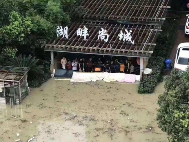 小區靠著簡單的沙包堤壩擋住了洪水。(取材自錢江晚報)