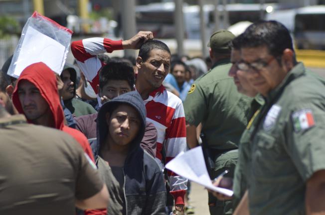 第一個被送回墨西哥提璜納等候庇護申請的移民,如今獲准留在美國。圖為美國邊界巡邏隊把一群申請庇護的移民送回墨西哥等待審批。(美聯社)