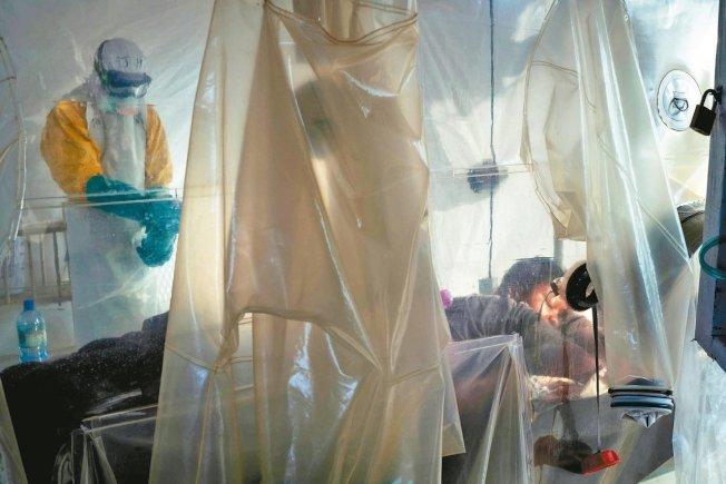 穿戴防護衣的醫護人員上月在剛果貝尼市檢查疑似伊波拉病毒患者。(美聯社)