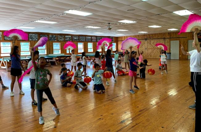 大紐約區中華文化夏令營邀請臺藝大碩士班顏子妘與陳采甯教民族舞蹈,學員們提著燈籠、舉著飄扇,樂在其中。(圖:夏令營提供)