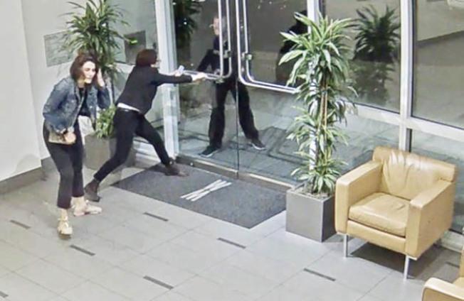 幾經辛苦,女管理員(中)緊握大門,女住客(左)才脫險,嫌犯(右)仍然在門外。(李華強提供)
