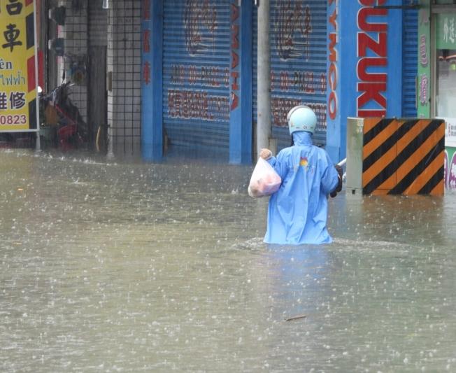部分災民不願意待在住處受困, 帶著貴重家當涉水離開。(記者周宗禎╱攝影)