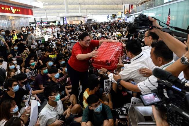 一名旅客欲搭機離港,但被眾多坐在機場出境大廳的示威者堵住去路,該名旅客將行李交給機場保安人員協助脫困。(Getty Images)