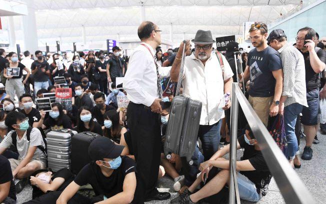 香港大批示威者13日以手推車等堵塞香港國際機場1號客運大樓旅客登機段及保安閘門,旅客未能經1號客運大樓前往離境大堂。( 中新社)